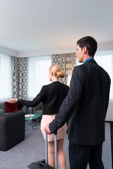 Mężczyzna i kobieta przyjeżdża w pokoju hotelowym