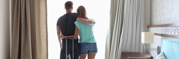 Mężczyzna i kobieta przytulają się przy oknie obok walizki