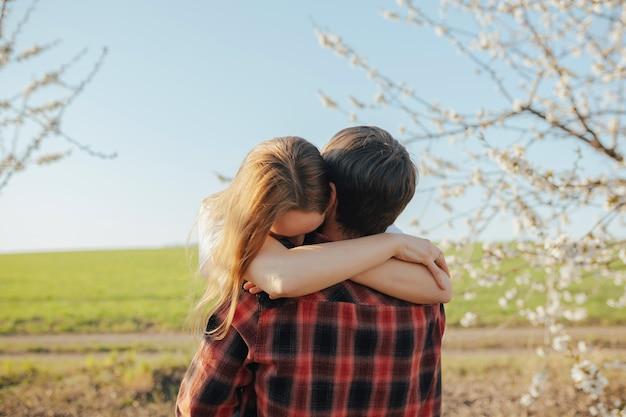 Mężczyzna i kobieta przytulanie w kwitnącym ogrodzie w wiosenny dzień z zielonym polem i niebieskim niebem