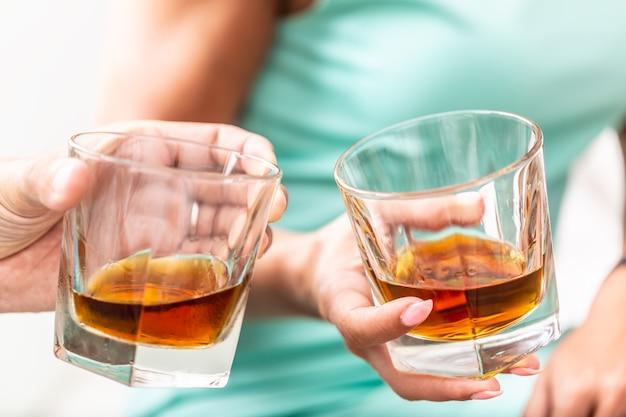 Mężczyzna i kobieta ręce opiekania z okularami whisky brandy lub rum w pomieszczeniu - zbliżenie.