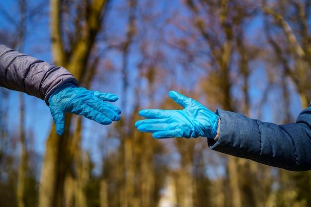 Mężczyzna i kobieta ręce w rękawiczkach medycznych rozciągają się do siebie. park z wysokimi drzewami rozmazane tło. selektywne skupienie. epidemia koronowirusa. covid-19 i identyfikacja koronawirusa. pandemia