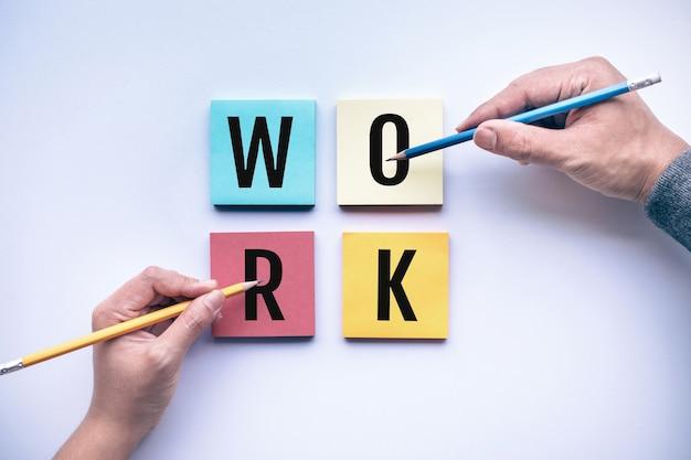 Mężczyzna i kobieta ręka ołówkiem i tekst pracy na tle koloru papieru firmowego