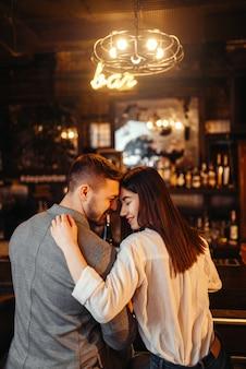 Mężczyzna i kobieta relaks, para przytula w barze. miłośnicy spędzają czas w pubie, mąż i żona relaksują się razem w nocnym klubie
