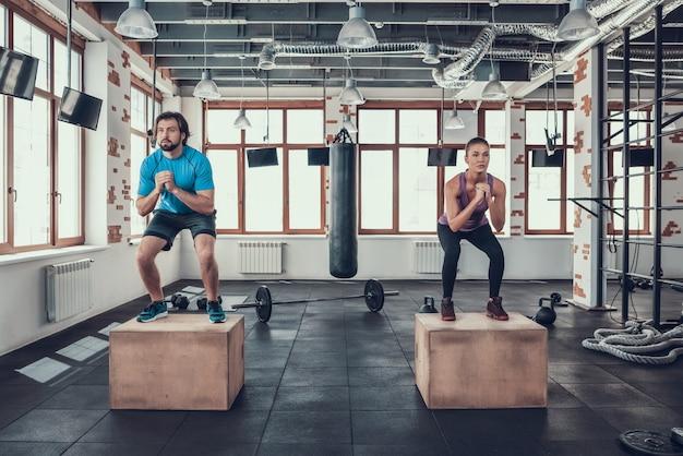 Mężczyzna i kobieta robi kucnięcia na blokach drewna w siłowni.