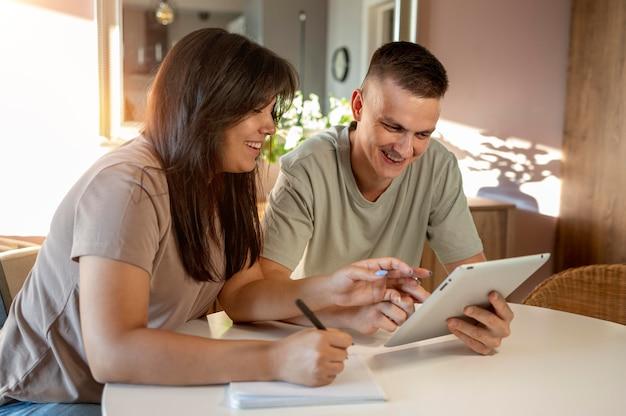 Mężczyzna i kobieta robią listę zakupów za pomocą tabletu