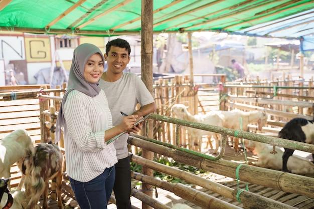Mężczyzna i kobieta rolnik w swoim gospodarstwie wspólnie sprawdzają stan zdrowia zwierząt