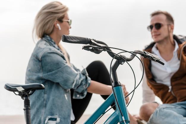 Mężczyzna i kobieta rozmawiają obok roweru na zewnątrz