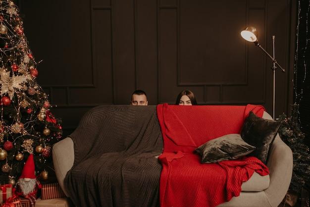 Mężczyzna i kobieta schowali się za kanapą. zza kanapy wystają głowy mężczyzny i kobiety.