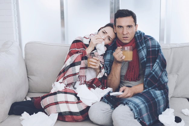 Mężczyzna i kobieta siedzą na kanapie i piją herbatę.