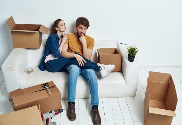 Mężczyzna i kobieta siedzą na kanapie, przenosząc pudełka z rzeczami rodzinnymi parapetówki