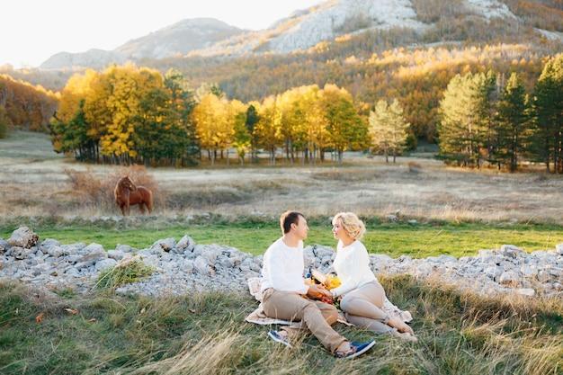 Mężczyzna i kobieta siedzą na kocu trzymając się za ręce na trawniku w jesiennym lesie pasący się koń