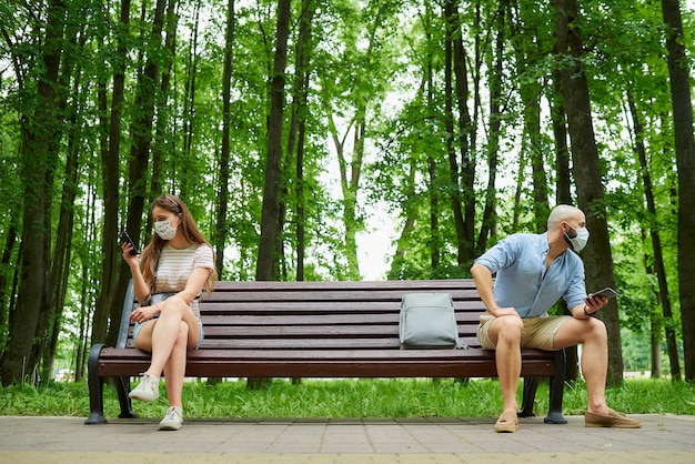 Mężczyzna i kobieta siedzą na przeciwległych końcach ławki, zachowując odległość od siebie, aby uniknąć rozprzestrzeniania się koronawirusa.
