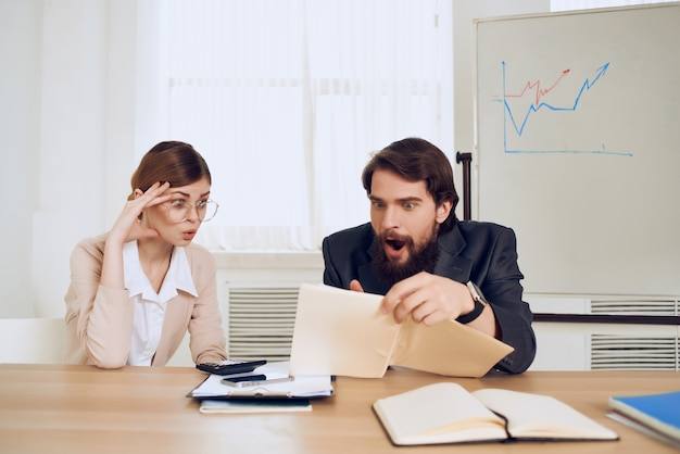 Mężczyzna i kobieta siedzą przy biurku dyskusja emocje komunikacja