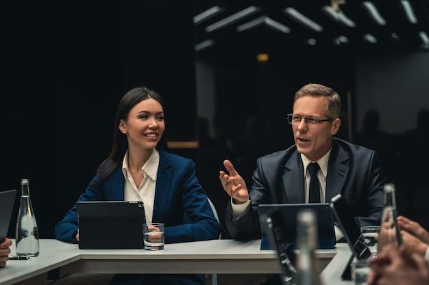 Mężczyzna i kobieta siedzą przy stole na spotkaniu biznesowym