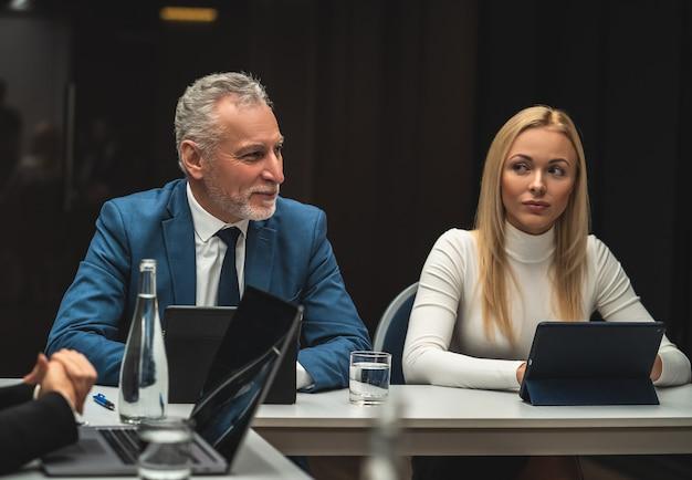 Mężczyzna i kobieta siedzą przy stole podczas konferencji biznesowej