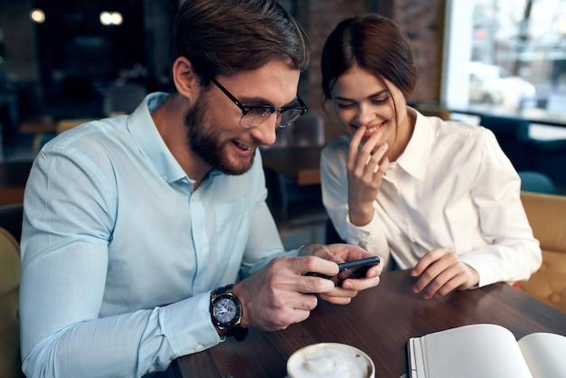 Mężczyzna i kobieta siedzą w kawiarni przy stole w pracy