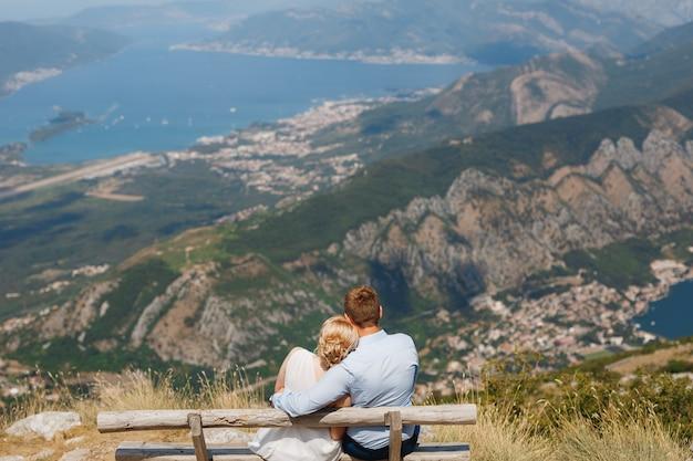 Mężczyzna i kobieta siedzą w objęciach na ławce, otwiera się panoramiczny widok na zatokę kotorską
