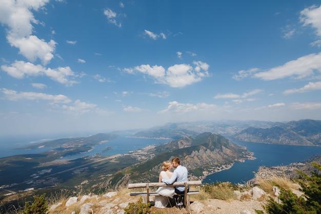 Mężczyzna i kobieta siedzą w objęciach na ławce, przed nimi otwiera się panoramiczny widok na zatokę kotorską. wysokiej jakości nagrania fullhd