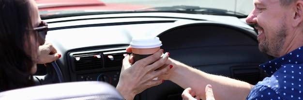 Mężczyzna i kobieta siedzą w samochodzie, uśmiechając się i trzymając szklankę kawy