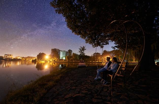 Mężczyzna i kobieta siedzi na ławce na brzegu w pobliżu jeziora pod drzewem. dobiera się cieszyć się widok nocne niebo pełno gwiazdy, milky sposób, spokojnej wody powierzchnia, miast światła na tle. koncepcja życia na świeżym powietrzu