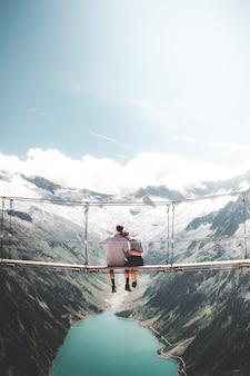 Mężczyzna i kobieta siedzi na wiszącym moście w ciągu dnia