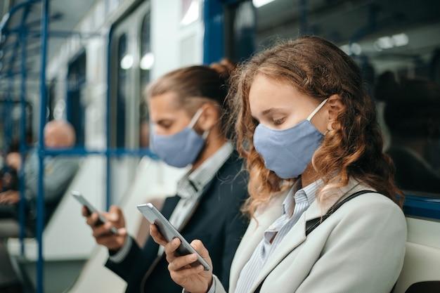 Mężczyzna i kobieta siedzi w wagonie metra ze smartfonami