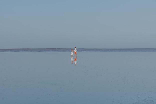 Mężczyzna i kobieta spacerują po gładkiej wodzie jeziora
