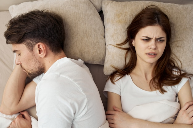 Mężczyzna i kobieta śpią w łóżku, telefonie, oszukiwaniu, związku miłosnym