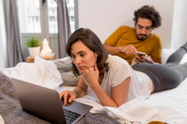 Mężczyzna i kobieta sprawdzają swoje urządzenia w domu