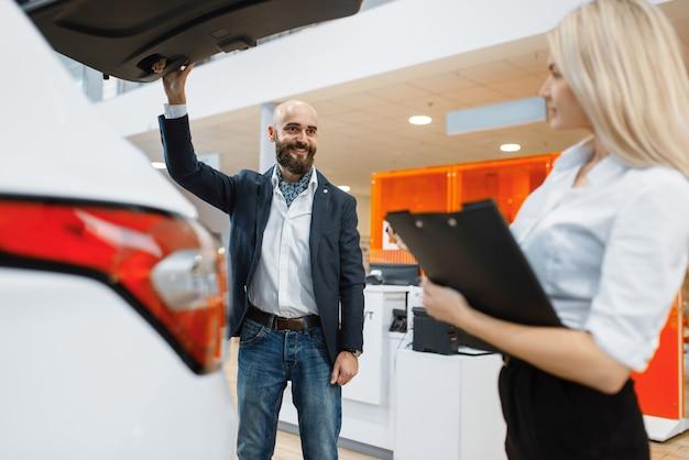 Mężczyzna i kobieta sprzedawca szuka auto w salonie samochodowym. klient i sprzedawczyni w salonie samochodowym, mężczyzna kupujący transport, firma dealera samochodowego