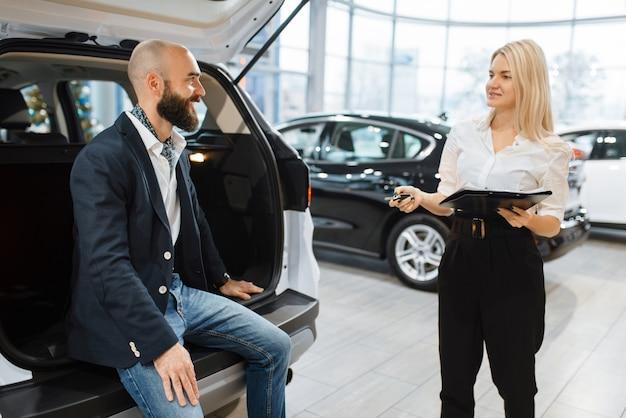 Mężczyzna i kobieta sprzedawca wybierając auto w salonie samochodowym. klient i sprzedawczyni w salonie samochodowym, mężczyzna kupujący transport, firma dealera samochodowego