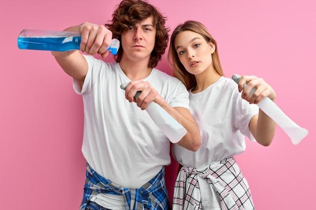 Mężczyzna i kobieta środki czyszczące w sprayu do czyszczenia na białym tle na różowym tle studio.