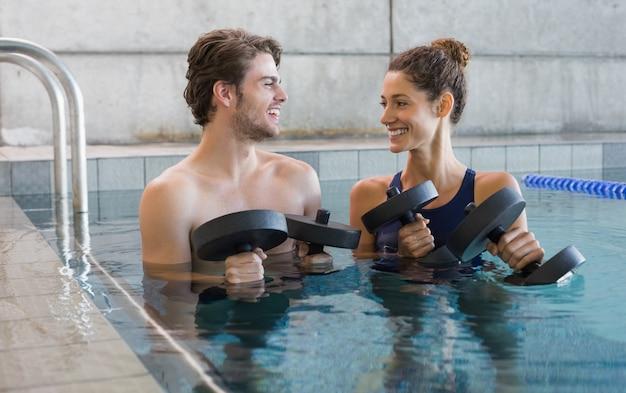 Mężczyzna i kobieta stoi z piankowymi hantlami w basenie