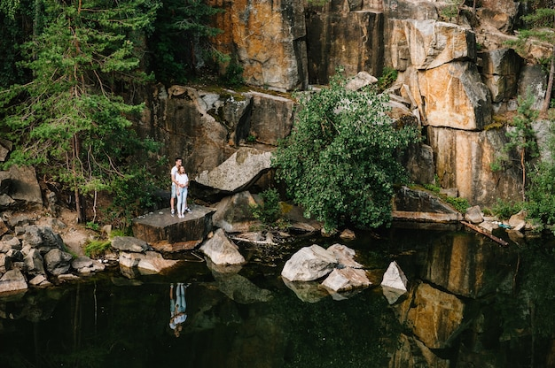 Mężczyzna i kobieta stoją i przytulają się na skałach, w pobliżu drzewa, lasu i jeziora