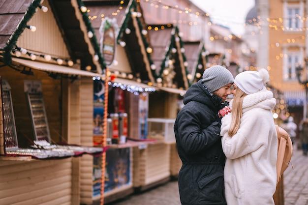 Mężczyzna i kobieta stoją, obejmując się na rynku udekorowanym przez boże narodzenie