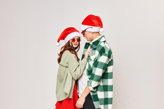 Mężczyzna i kobieta stoją obok noworocznych czapek z modnymi okularami przeciwsłonecznymi