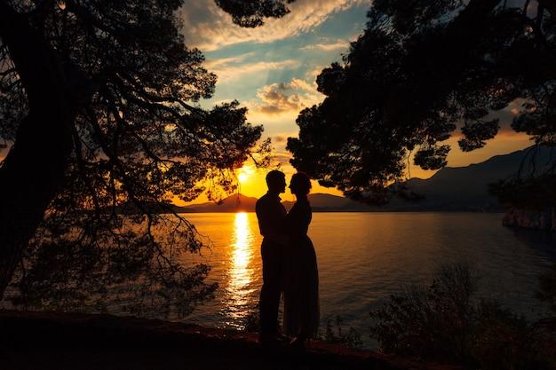 Mężczyzna i kobieta stoją trzymając się za ręce na brzegu morza na tle gór o zachodzie słońca