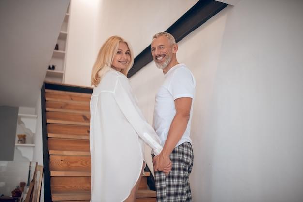 Mężczyzna i kobieta stojąc na schodach i patrząc podekscytowany