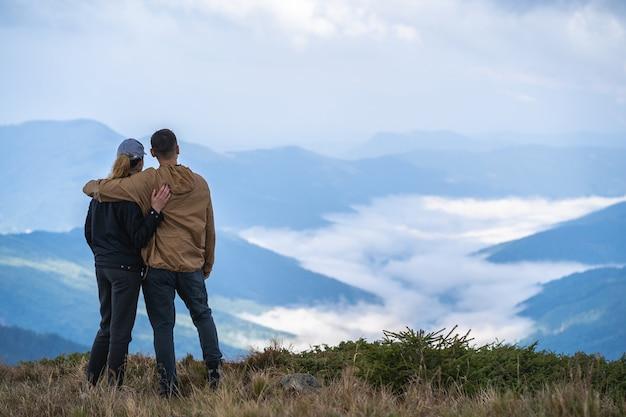 Mężczyzna i kobieta stojący na tle górskiego krajobrazu