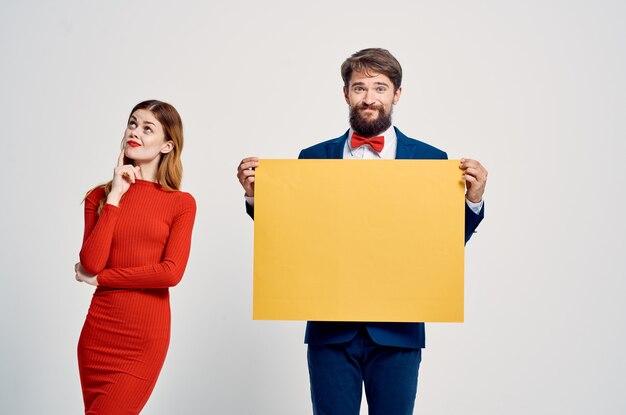 Mężczyzna i kobieta stojący obok siebie reklamujący żółty plakat makieta jasnym tle