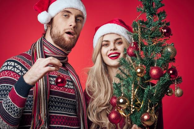 Mężczyzna i kobieta świąteczne zabawki świąteczne dekoracje czerwone tło