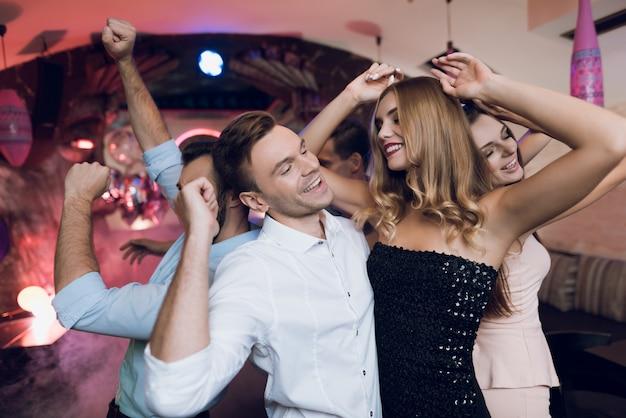 Mężczyzna i kobieta tańczą na pierwszym planie.
