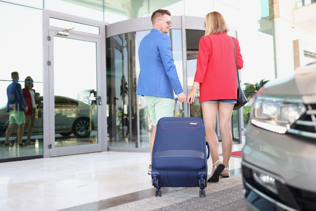 Mężczyzna i kobieta toczą walizkę obok samochodu.