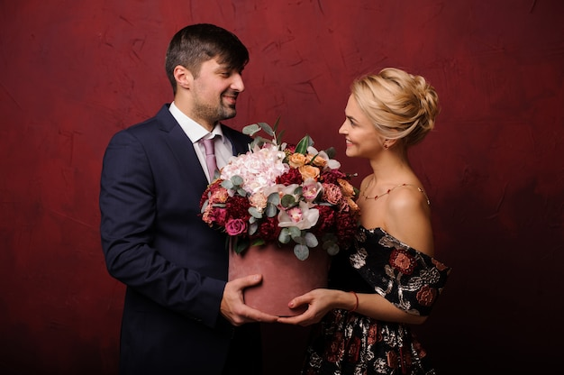 Mężczyzna i kobieta trzyma bukiet kwiatów patrząc w oczy