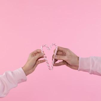 Mężczyzna i kobieta trzyma cukierki laski w formie serca