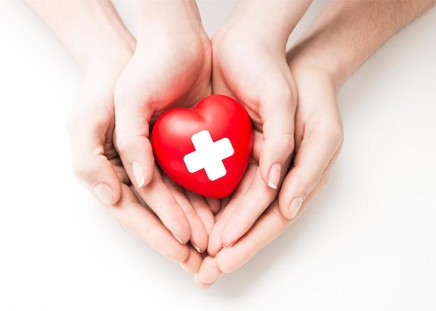 Mężczyzna i kobieta trzyma czerwone serce w rękach na białym tle