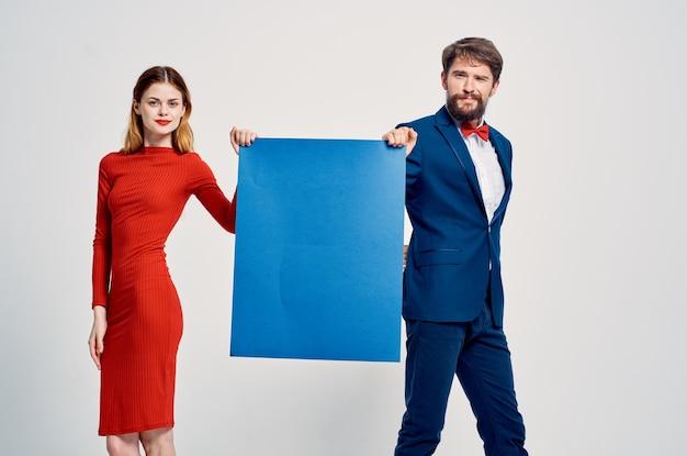 Mężczyzna i kobieta trzyma niebieski plakat makieta reklamowa miejsce na kopię