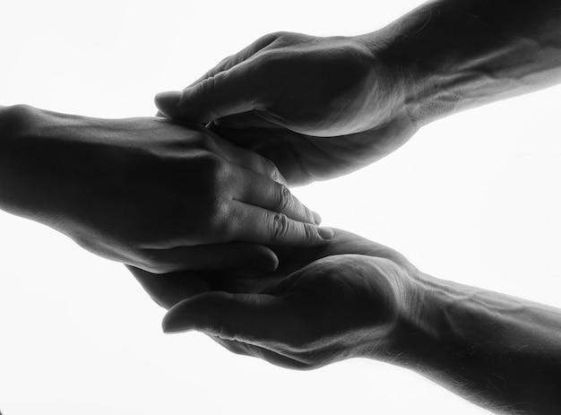 Mężczyzna i kobieta trzymać ręce - czarno-biały sylwetka na białym tle.