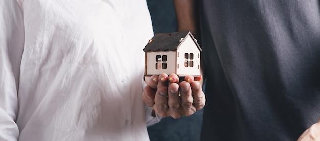 Mężczyzna i kobieta trzymają dom