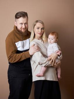 Mężczyzna i kobieta trzymają dziecko w ramionach. portret pary małżeńskiej po urodzeniu dziecka. młoda rodzina